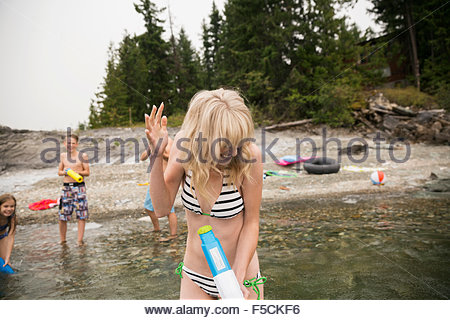 Playful family with water guns in lake - Stock Photo
