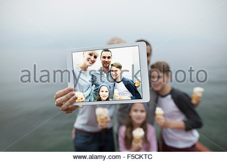 Family eating ice cream taking selfie lakeside - Stockfoto