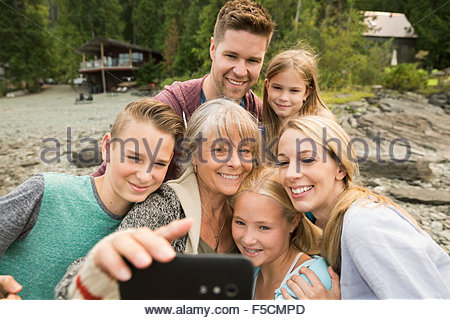 Multi-generation family taking selfie outside cabin - Stockfoto