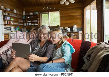 Multi-generation women using digital tablet cabin sofa - Stock Photo