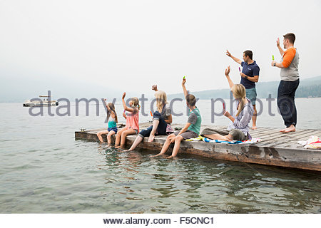 Family on dock waving to boat on lake - Stockfoto