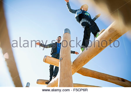 Father and son balancing logs sunny playground - Stock Photo