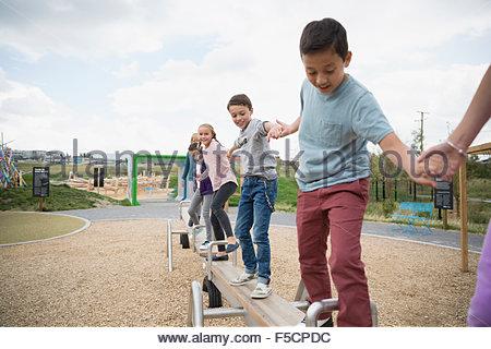 Kids balancing on long seesaw at playground - Stock Photo