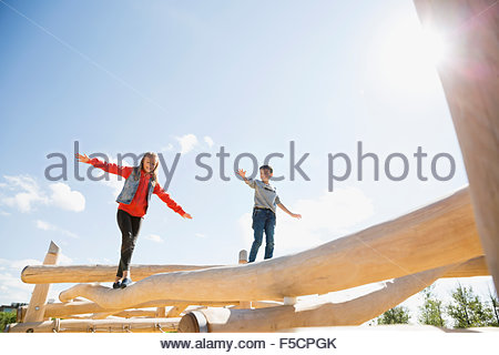 Boy and girl balancing logs sunny playground - Stock Photo
