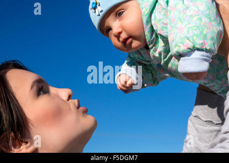 Mother and baby on blue sky background - Stock Photo