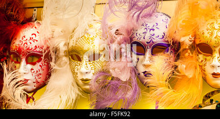 Colourful feathered masks for Venice Carnival on sale as tourist souvenirs, Venice, Italy - Stock Photo