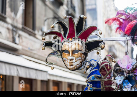 Colourful jester mask for Venice Carnival on sale as a tourist souvenir, Venice, Italy - Stock Photo