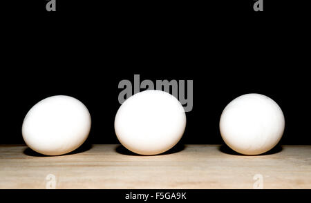 three eggs in a row on a chopping board - Stock Photo