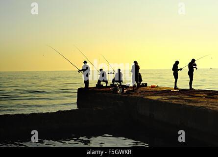 Group of fishermen on a pier at sunset. Crimea peninsula - Stockfoto