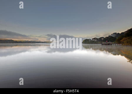 The Pier at Howtown on Ullswater lake during mist at dawn, Lake District National Park, Cumbria, England, Uk, Gb. - Stock Photo