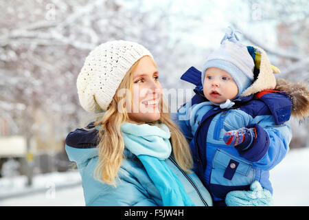 happy mother and baby in winter park - Stock Photo