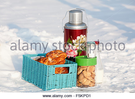 Sweden, Uppland, Thermos, milk bottle, cookies and sweet buns in basket - Stock Photo