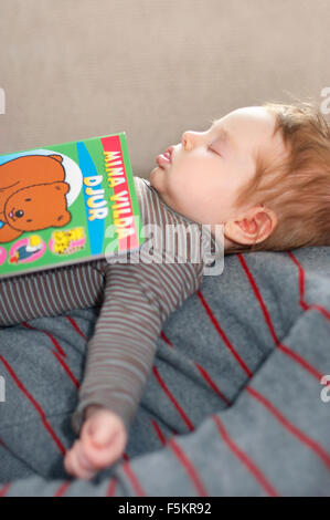 Sweden, Vastra Gotaland, Gothenburg, Girl (12-17 months) sleeping with book on father's chest - Stock Photo