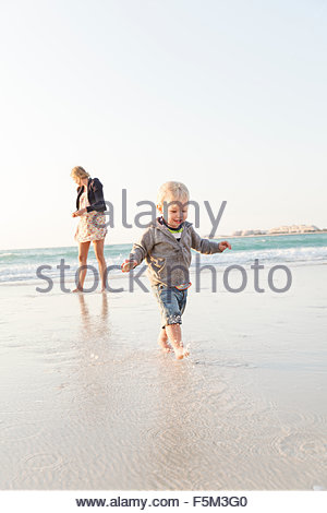 United Arab Emirates, Dubai, Woman with son (12-17 months) on beach - Stockfoto