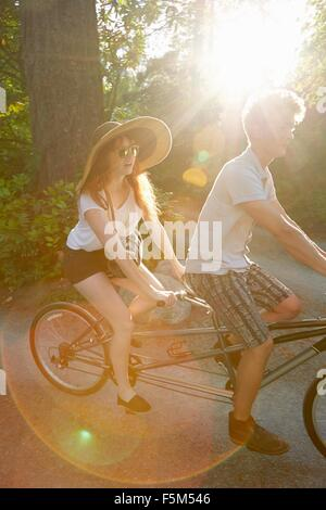 Young couple cycling on tandem cycle along rural road - Stock Photo