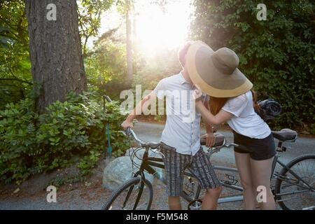 Young couple with tandem cycle kissing on rural road - Stockfoto