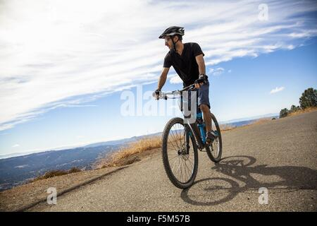 Young male mountain biker looking out at view from rural road, Mount Diablo, Bay Area, California, USA - Stock Photo