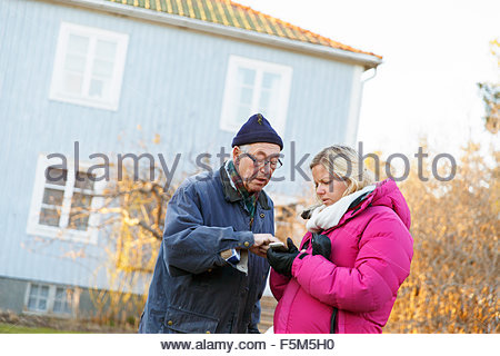 Sweden, Sodermanland, Jarna, Man and woman looking at phone - Stock Photo