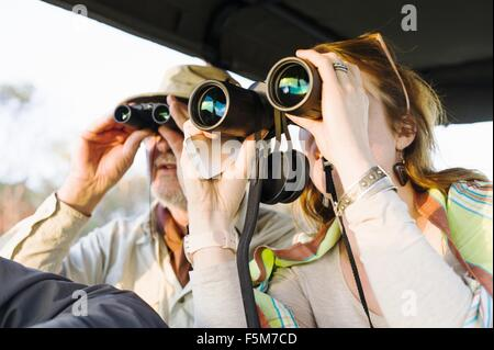 Senior man and daughter looking out through binoculars on safari, Kafue National Park, Zambia - Stock Photo