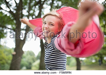 Portrait of young woman with arms open wearing pink shirt - Stock Photo