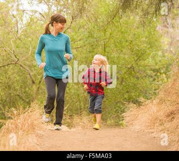 Mother and son running in forest - Stock Photo