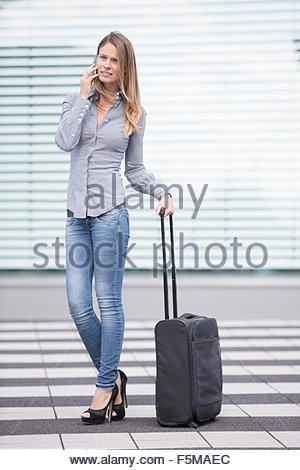 Young businesswoman with wheeled suitcase chatting on smartphone at airport - Stock Photo