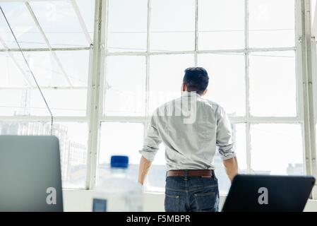 Businessman looking out of office window - Stockfoto
