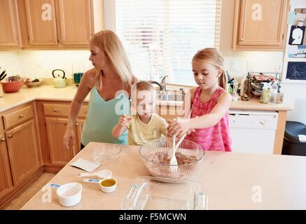 Family preparing batter in mixing bowl - Stock Photo