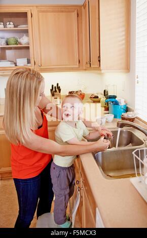 Mother washing son's hands in kitchen sink - Stock Photo
