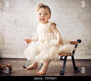 Elegant little girl sitting on the tiny bench - Stockfoto