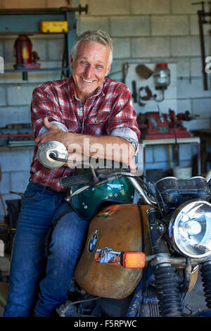 Mature aged man sits on his motorbike in his shed / workshop - Stock Photo
