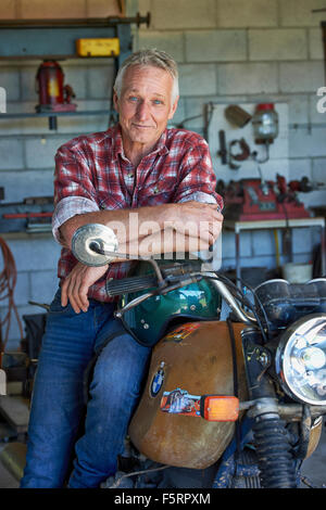 Mature aged man sits on his Motorbike in his shed/workshop - Stock Photo