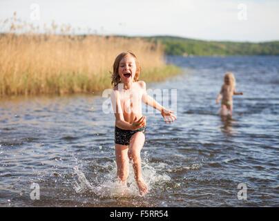 Sweden, Vastergotland, Lerum, Lake Aspen, Boy (8-9) and girl (6-7) playing in lake - Stockfoto