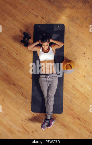 Fit young woman lying on exercise mat doing stomach exercises. Overhead view of female working out at the gym - Stockfoto