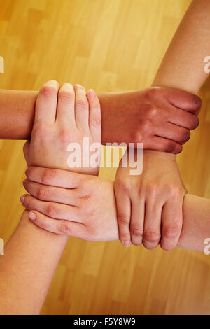 Four hands holding each other at the wrists - Stock Photo