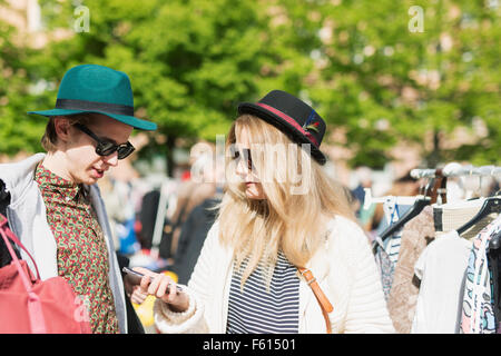 Young woman showing mobile phone to friend while standing at flea market - Stock Photo