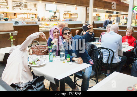 Happy friends taking selfie while having food at cafe in railroad station - Stock Photo