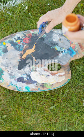 Cropped image of senior woman with palette and painting knife in backyard - Stock Photo
