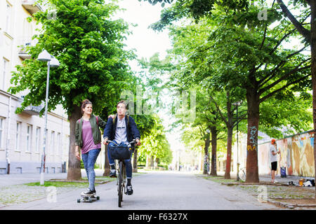 Woman skateboarding while riding bicycle on street - Stock Photo
