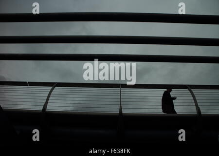 people walking on the  Millennium Bridge in London on a Rainy day - Stock Photo