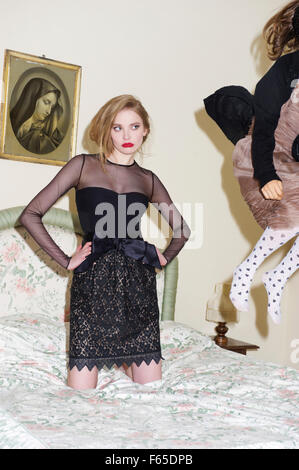 Contemplative woman wearing transparent top and lace skirt kneeling on bed, hands on hip - Stock Photo