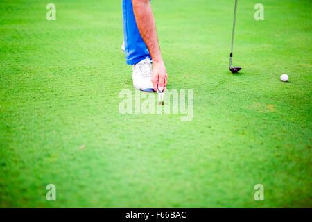 Golf player repairing divot on a green grass surface - Stock Photo