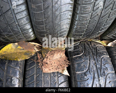 Close up of textured rubber tyres with  leaves - Stock Photo
