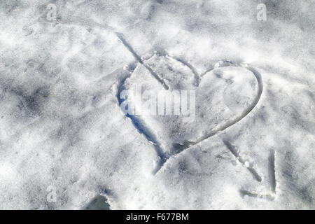 heart pierced by an arrow drawn in the snow - Stockfoto
