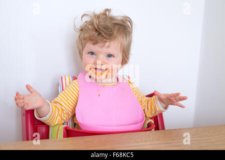 One year old baby eating messily, England, UK - Stock Photo