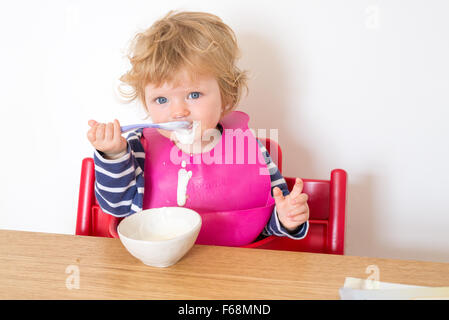 One year old baby eating yoghurt messily with a spoon, England, UK - Stock Photo