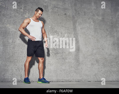 Male fitness model in white tank top relaxing after workout. Grey background with room for text, Copy space - Stock Photo