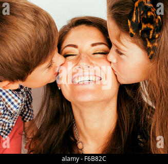 two pretty children kissing their mother close up, happy family - Stock Photo