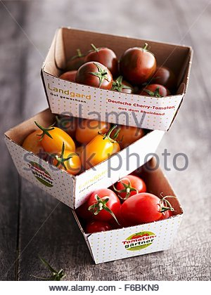 Various mini tomatoes in cardboard boxes - Stock Photo