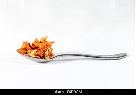 A spoonful of butternut squash seeds against a white background - Stock Photo